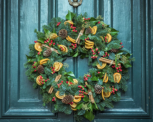 A colourful Christmas wreath hanging on a green door.