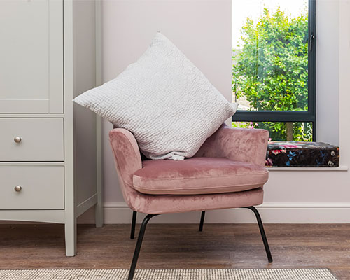 Blush pink chair with white cushion and view of the trees out of the window.