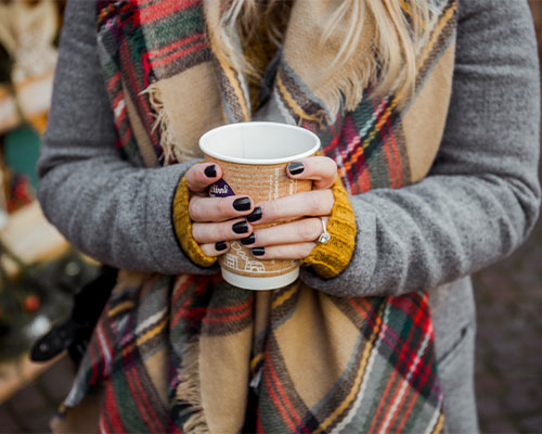 Woman holding a cup of something warm.