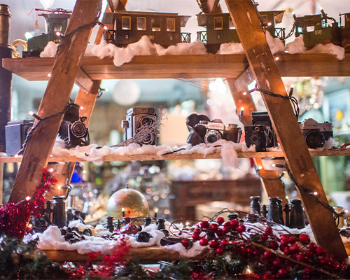 A beautifully decorated Christmas stall with fake snow and berries.
