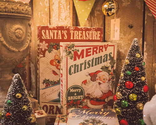 Mini Christmas trees and Merry Christmas signs and other decorations available to buy at Christmas market stall.