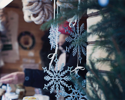 Snowflake decorations hanging from a Christmas market stall,