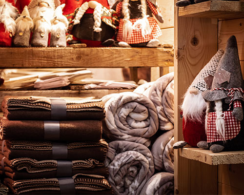 A close up of the products available to buy at the Christmas market such as cosy blankets and decorations.