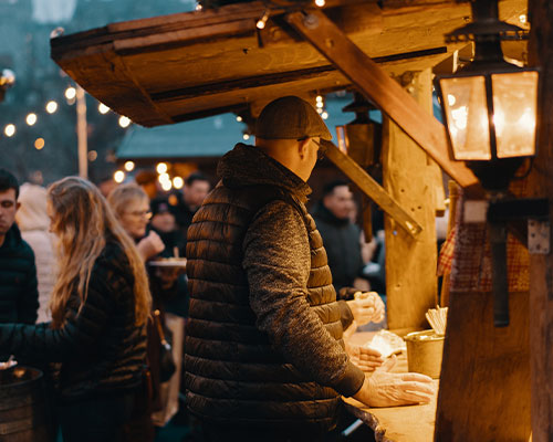 Man standing at a stall in a Christmas Market with festive lights and other shoppers surrounding him.
