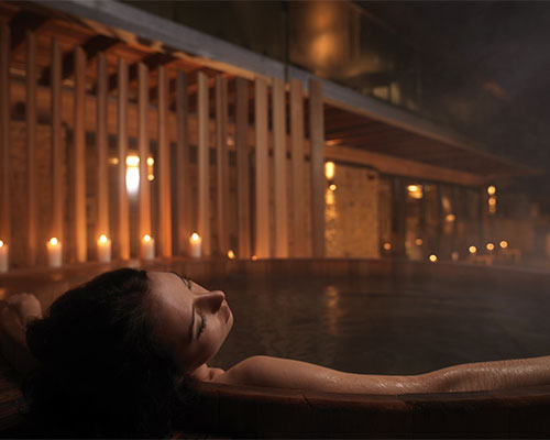 Woman relaxing in spa treatment room.