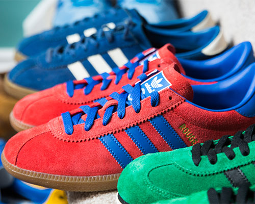 A red pair, green pair and blue pair of Adidas trainers.