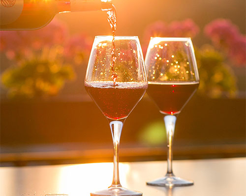 Two glasses of wine being poured in the sun